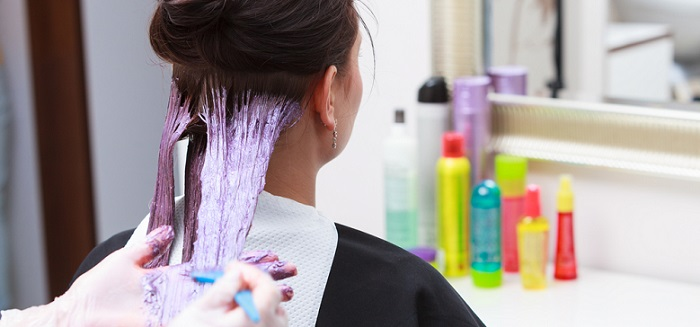 professional hairdressers applying hair dye on a client's hair
