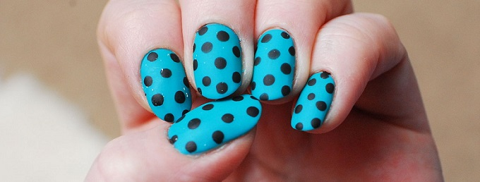 a woman's hand wearing polka dots polish on her nails