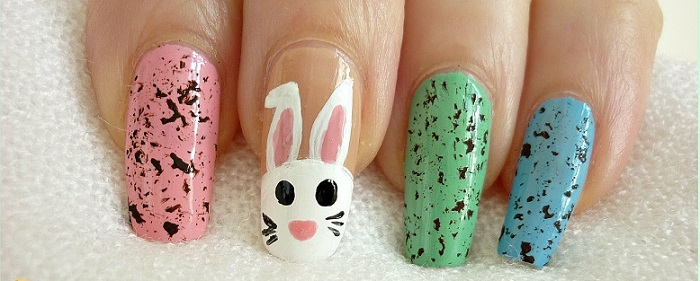 an Easter manicure with a bunny and speckled nails