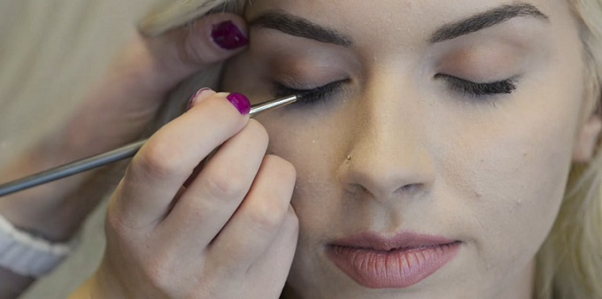 a professional beauty expert applying eyeliner to a woman