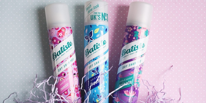 three cute-looking bottles of Batiste dry shampoo on a pink background