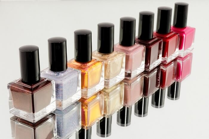 collection of colorful nail polish bottles on mirror