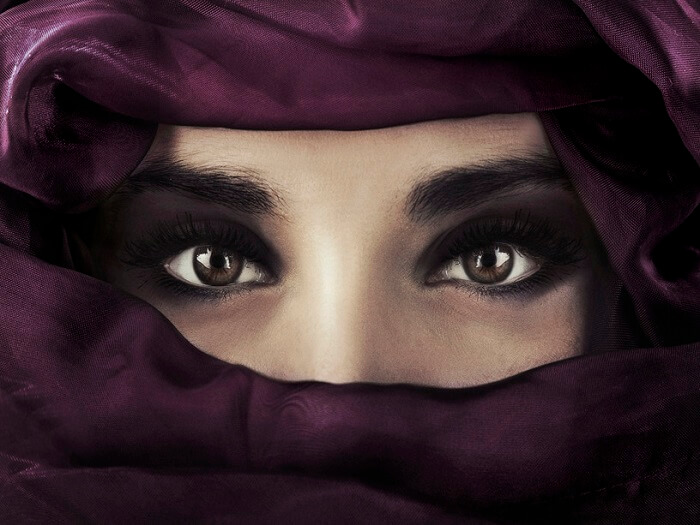 close up on beautiful woman's face with arabic makeup and arabic scarf