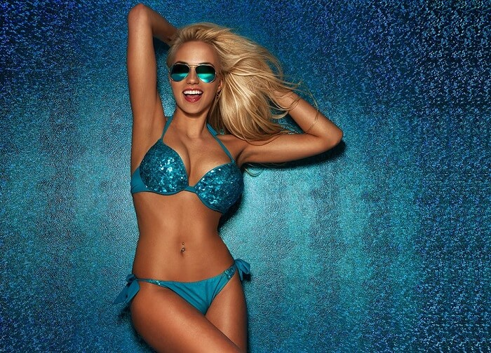 blonde woman in blue bikini posing happy with sunglasses