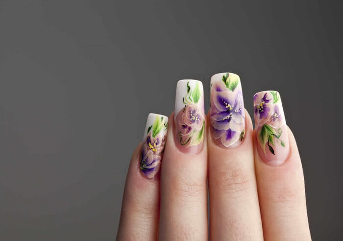 nail art on one hand with spring flowers motives