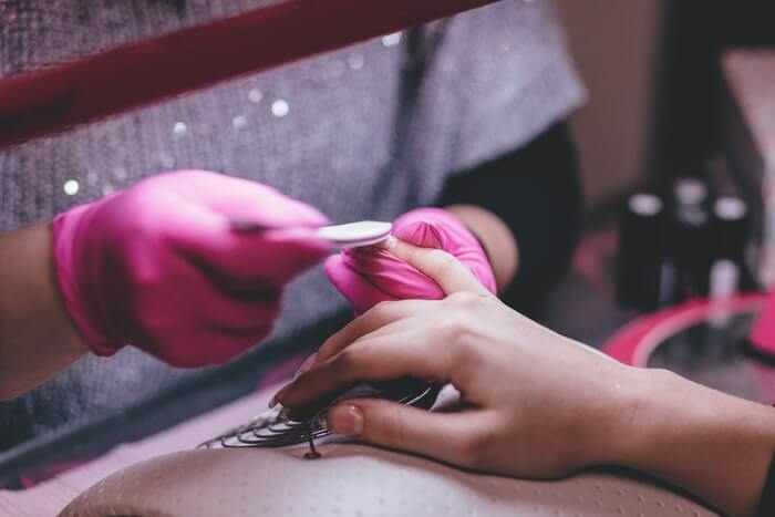 close up of a professional doing manicure to a woman in salon