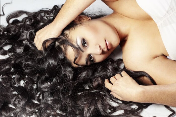 beautiful brunette woman laying down with long stylish curls spread on white sheet