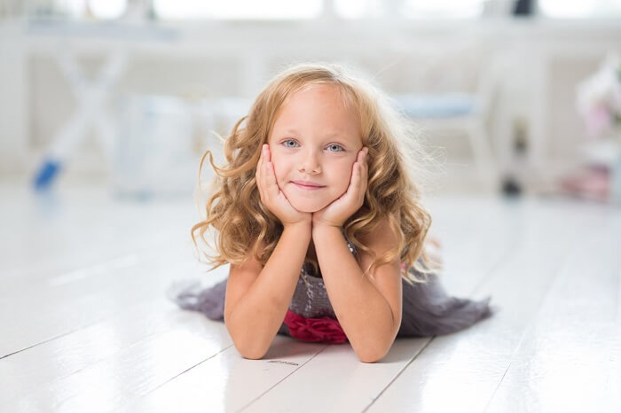 beautiful little girl with long blonde curls lying on the floor of her bedroom