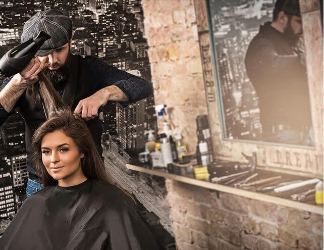 male hair stylist blow dries a female model at  a hair salon