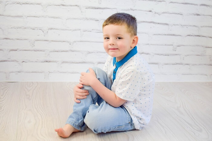 happy small boy in light colored clothes standing barefoot on the floor of a white room