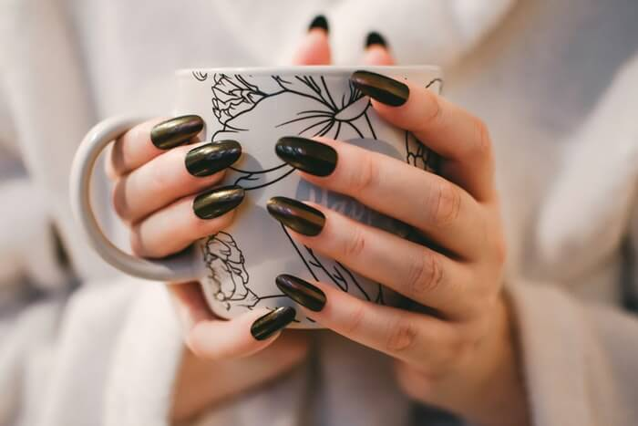 cropped woman with black manicure holding mug
