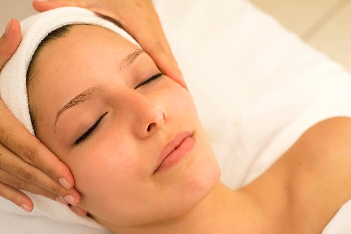 relaxed beautiful woman receiveing head massage at salon
