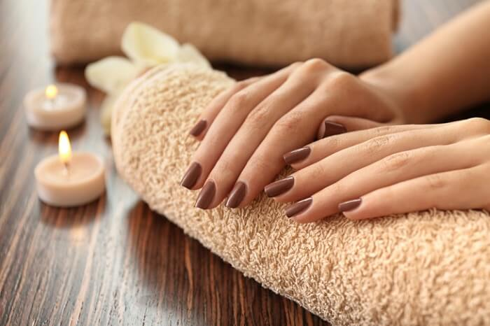 cropped woman's hands with brown manicure on bath towel with candles nearby