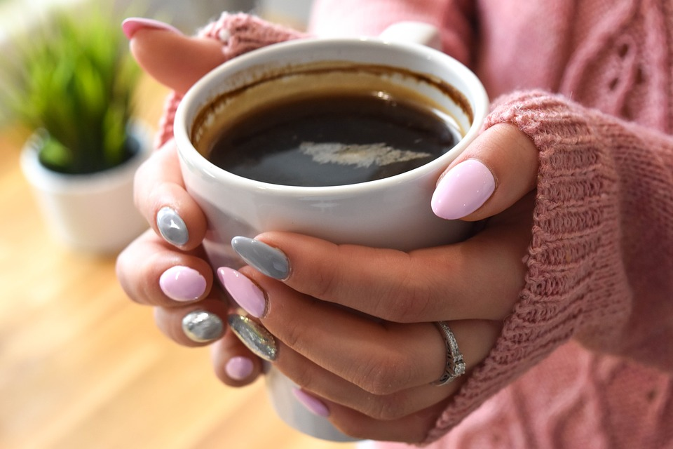 Image of person with powder nails manicure holding a cup of coffee.