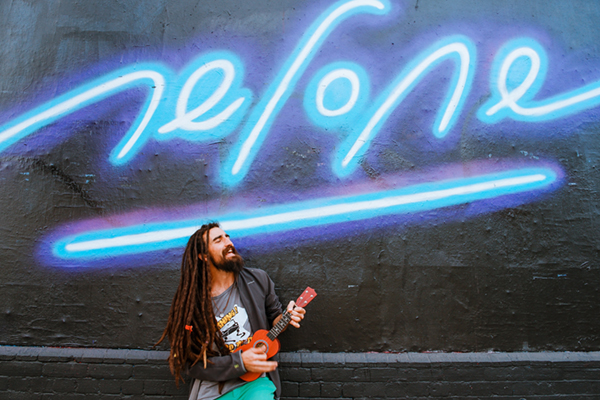Man with dreadlocks hairstyle is holding a guitar