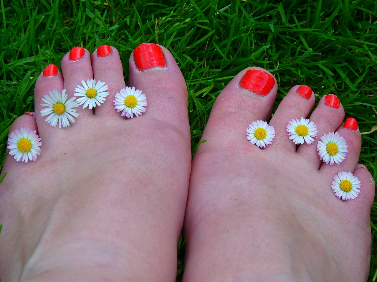 Foot having red nail polish and a flower on each toes