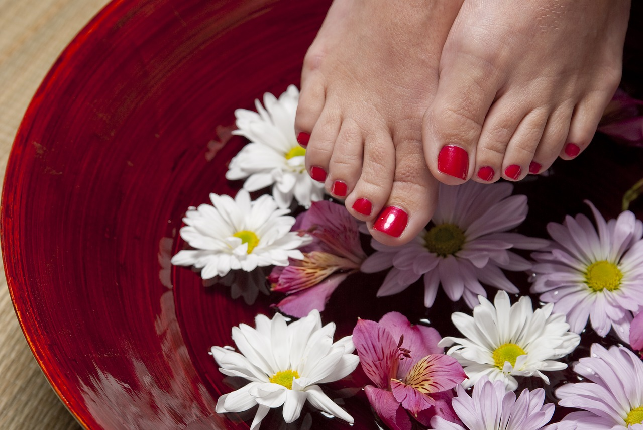 A foot with red nail color attempting to soak on a bowl of water with flower