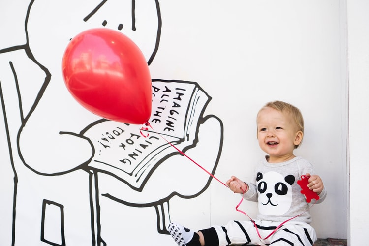 smiling toddler holding red balloon