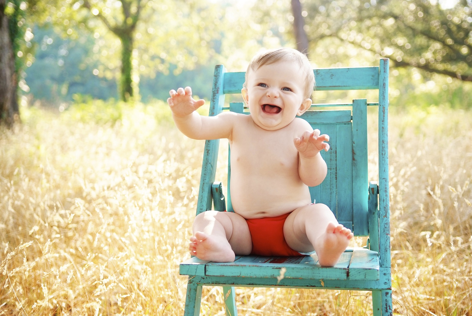 A baby sitting outside in a chair wearing nothing but a diaper and suncreen for babies